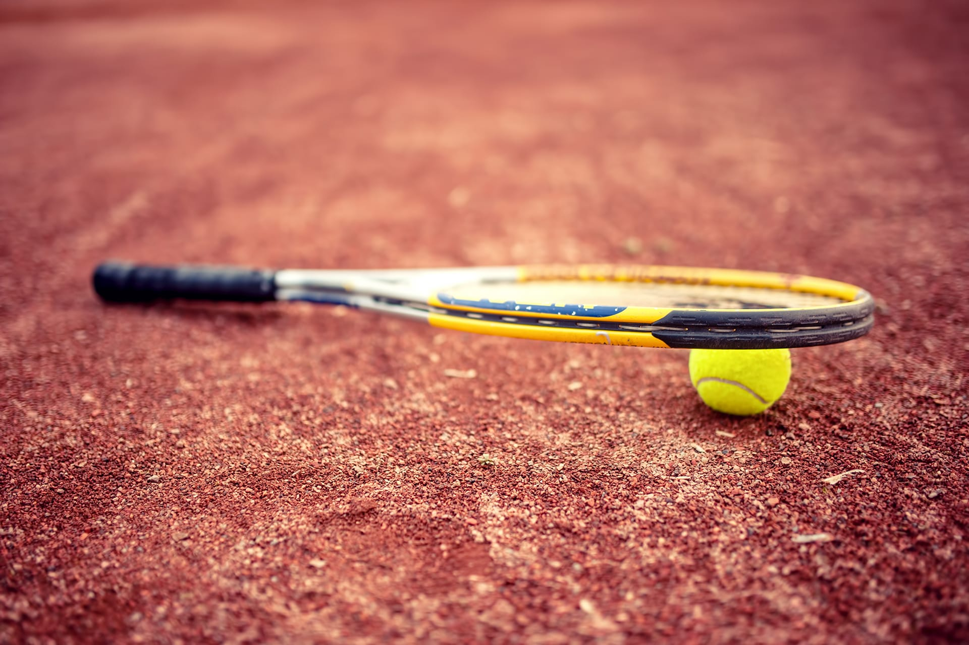 close up of tennis racket and ball on clay tennis PV4U4NT